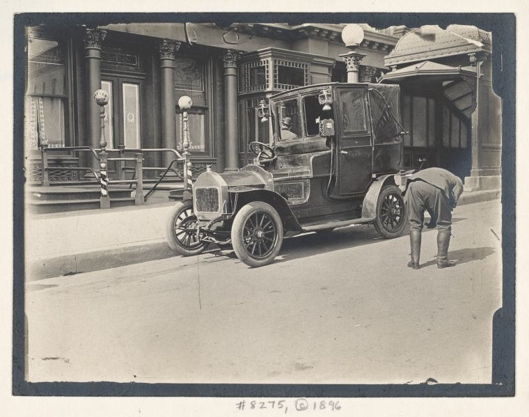 Taxi driver inspecting his vehicle. (1896)
