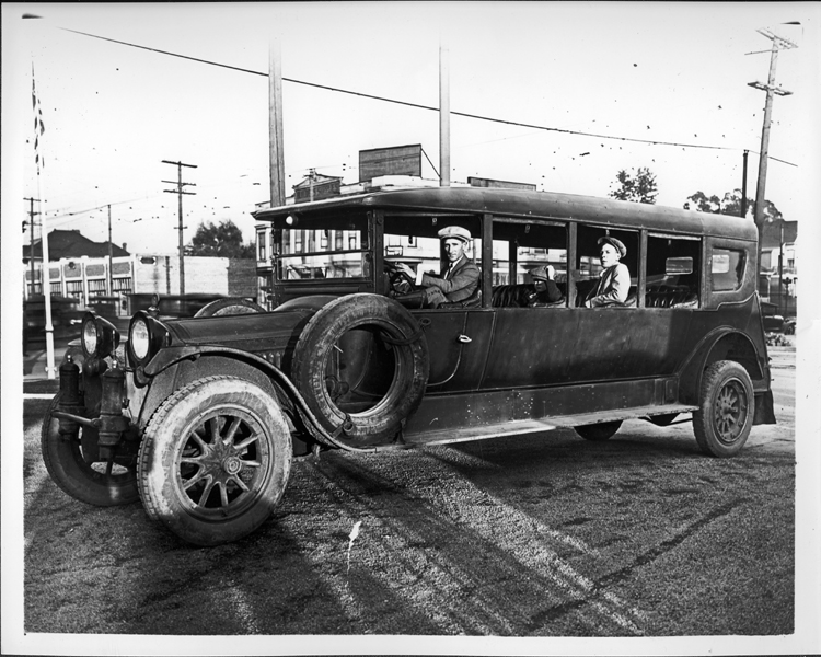 1915-16 Packard jitney bus, parked on street, man behind wheel, two male passengers MI