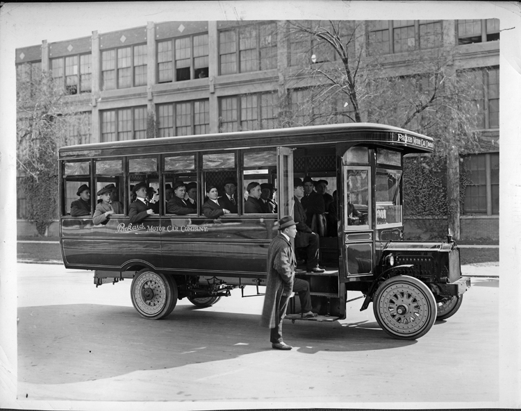 1917 Packard jitney bus full of male passengers, parked on street MI