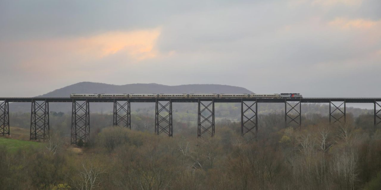 Пригородный поезд компании NJ Transit ползет по железнодорожному виадуку Мудна в штате Нью-Йорк